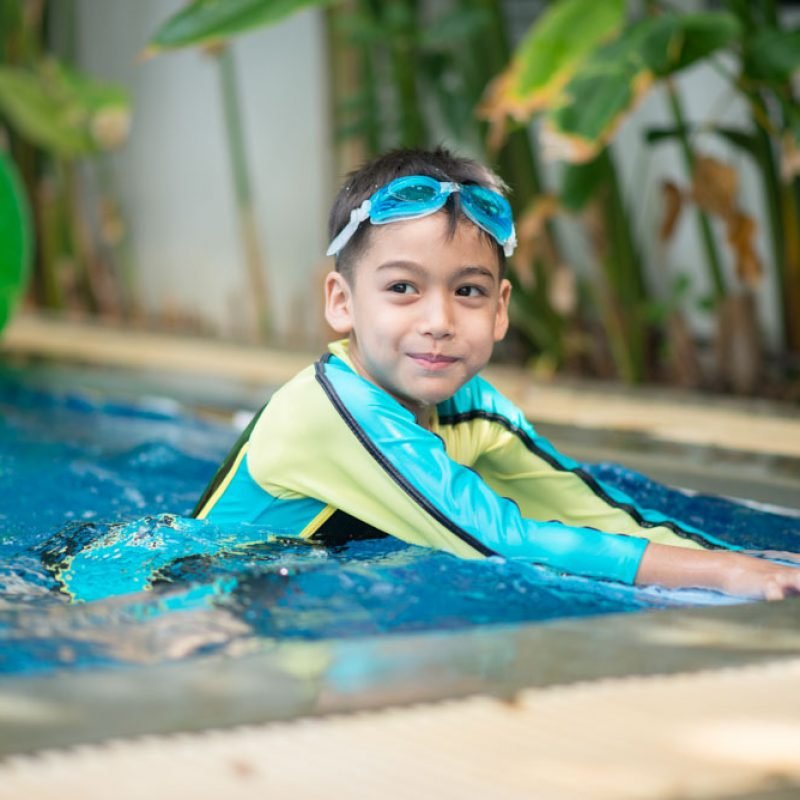 Little mix Asian Arab boy swimming at swimming pool in the hotel outdoor activity