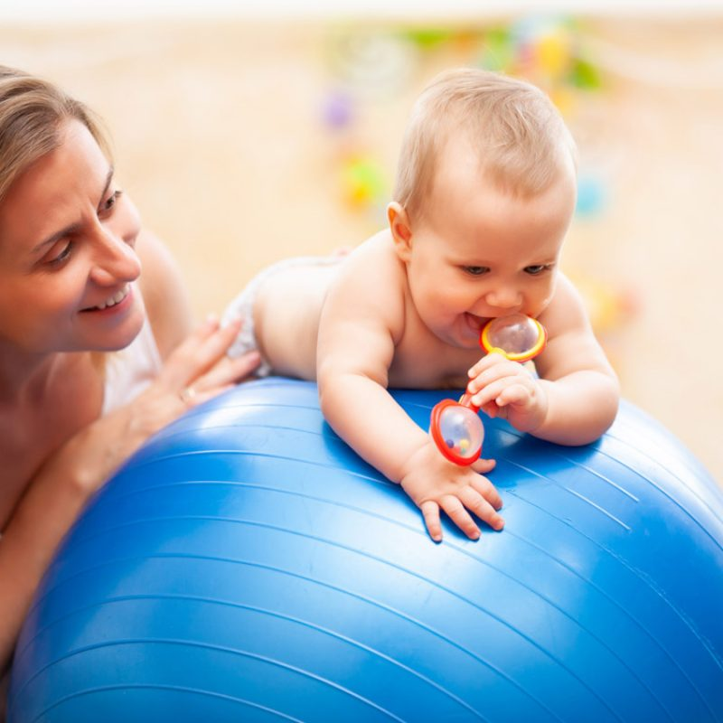 Selective focus of cute little toddler lying on big blue fitness ball and holding red toy. Front view of naked caucasian kid practicing gymnastics for babies, happy mother helping on background.