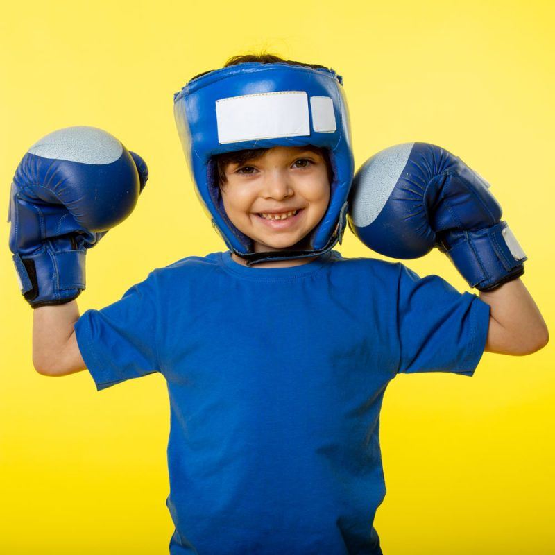 a front view smiling cute boy in blue boxing gloves blue boxing helmet and in blue t-shirt on the yellow desk
