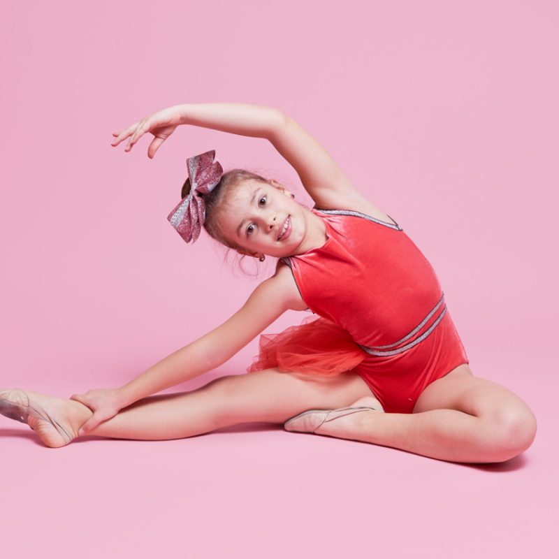Young gymnast cheerleader girl doing an exercise on pink background. childrens professional sports. Cheerleading