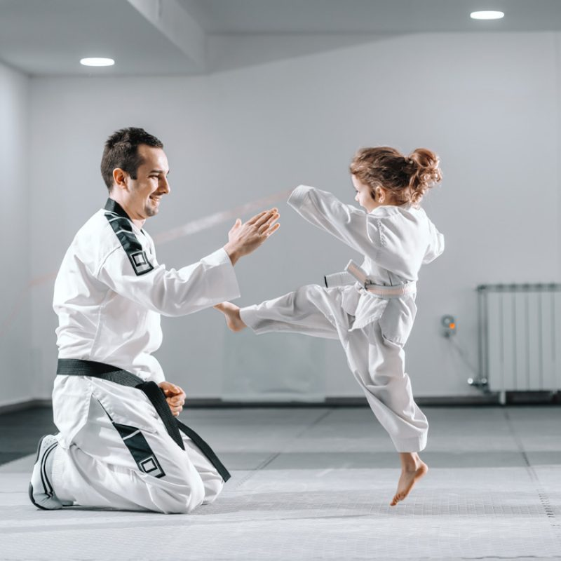 Smiling Caucasian taekwondo trainer in dobok kneeling and holding hand up while little girl kicking him.